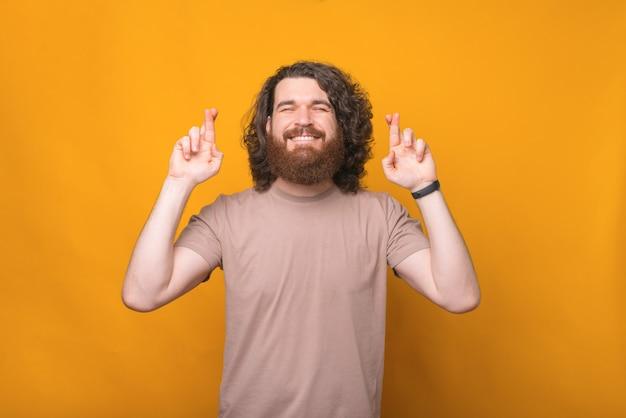 Retrato de um jovem barbudo hippie com cabelo comprido e encaracolado cruzando os dedos sobre o amarelo