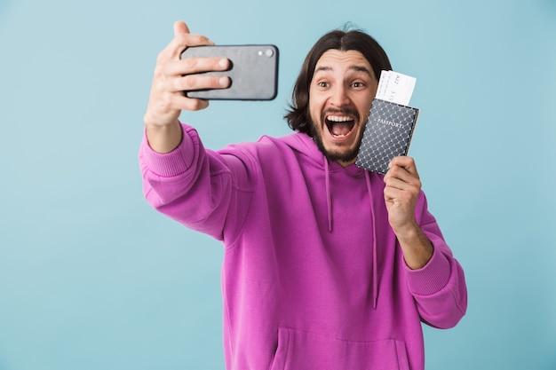 Retrato de um jovem barbudo, jovem e feliz, moreno com capuz isolado na parede azul, tirando uma selfie, mostrando o passaporte com os ingressos