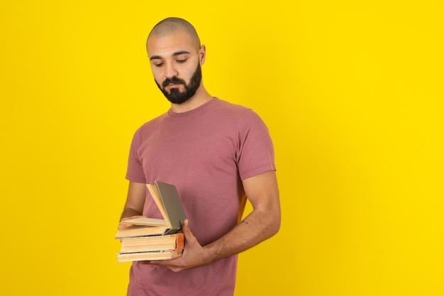 Retrato de um jovem barbudo segurando livros sobre a parede amarela.