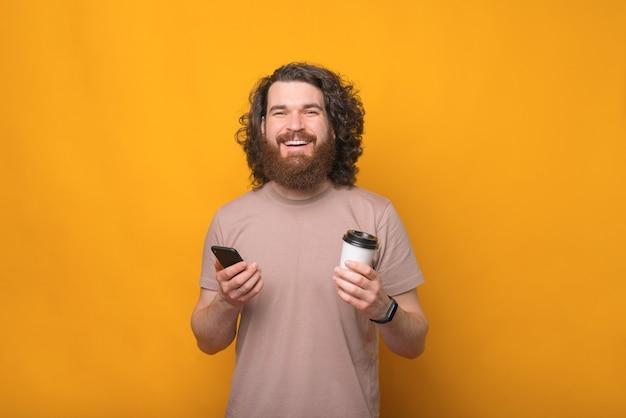 Retrato de um jovem barbudo sorridente e alegre segurando um smartphone e um café para viagem