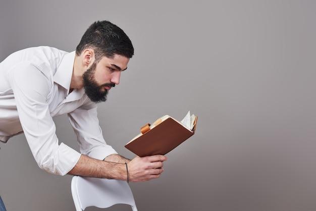 Retrato de um jovem barbudo, vestindo uma camisa branca e segurando um planejador aberto e uma caneta. uma parede cinza