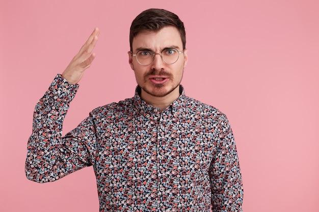Retrato de um jovem bonito barbudo com uma expressão facial agressiva e raivosa, tem tempo para provar seu ponto de vista, explica o ponto de vista.