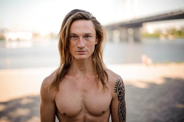 Retrato de um jovem bonito cabelo comprido na praia