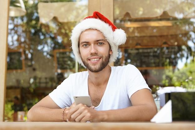 Retrato de um jovem bonito com a barba por fazer usando um chapéu vermelho com pelo branco segurando um telefone celular