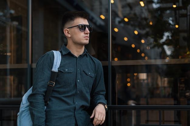 Retrato de um jovem bonito com óculos escuros e mochila