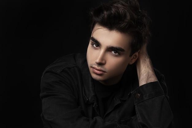 Retrato de um jovem bonito, confiante. veste roupas pretas.