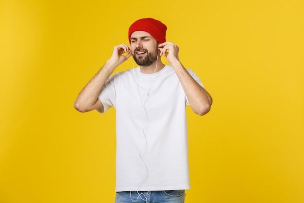 Retrato de um jovem bonito, dançando e ouvindo música, isolada em amarelo.