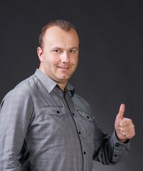 Retrato de um jovem bonito dando o polegar para cima em um fundo cinza