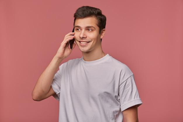 Retrato de um jovem bonito de olhos castanhos em uma camiseta cinza olhando para o lado com um sorriso sincero encantador, segurando o celular na mão e tendo uma conversa agradável, em pé sobre um fundo rosa