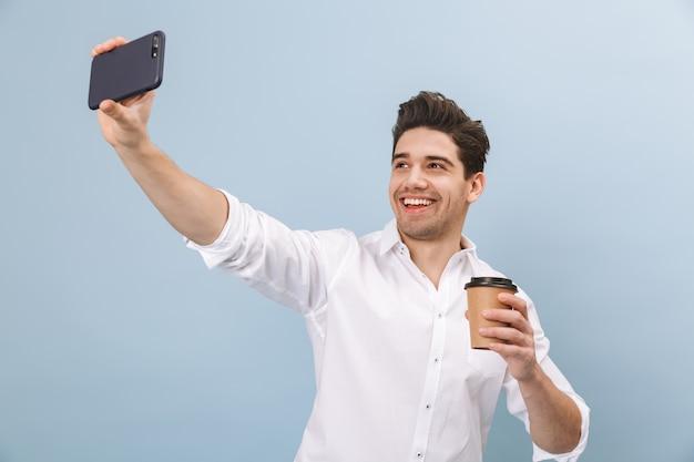 Retrato de um jovem bonito e alegre em pé isolado em um azul, segurando uma xícara de café para viagem, tirando uma selfie