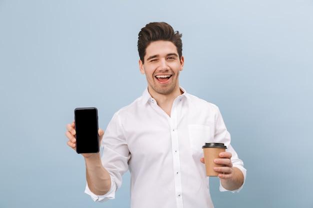 Retrato de um jovem bonito e alegre, isolado em um azul, segurando uma xícara de café para viagem, mostrando a tela em branco do celular