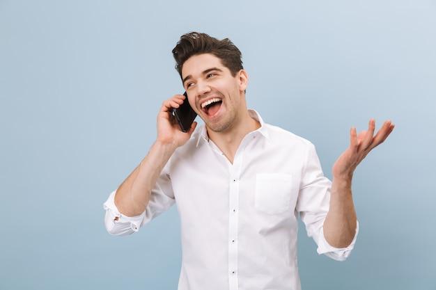 Retrato de um jovem bonito e alegre, isolado em uma azul, falando no celular