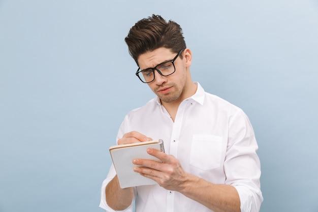 Retrato de um jovem bonito e alegre usando óculos, isolado no azul, fazendo anotações
