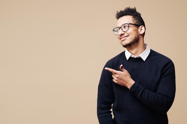 Retrato de um jovem bonito e sorridente homem afro de óculos, sorrindo e em pé com um gesto de mão aberta isolado na parede bege