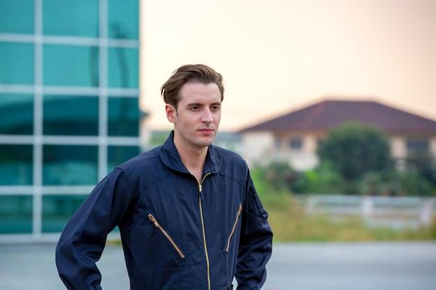 Retrato de um jovem bonito em gesto uniforme de engenheiro técnico contra o aeroporto