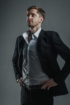 Retrato de um jovem bonito em uma camisa branca e terno escuro.