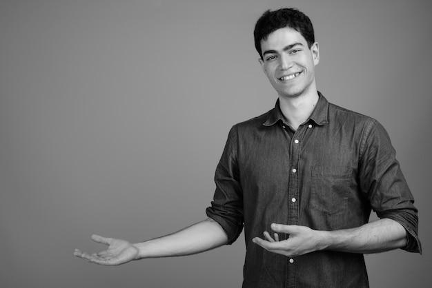 Retrato de um jovem bonito empresário persa feliz mostrando algo