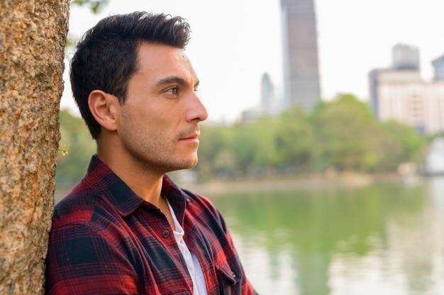 Retrato de um jovem bonito hispânico moderno no parque ao ar livre