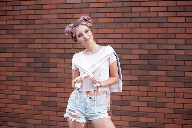 Retrato, de, um, jovem, bonito, menina, com, cabelo cor-de-rosa, coque, sorrindo, contra, um, parede tijolo vermelho