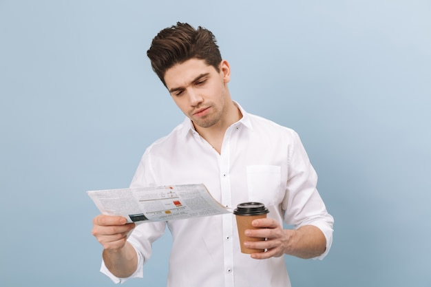 Retrato de um jovem bonito pensativo em pé, isolado no azul, segurando uma xícara de café para viagem
