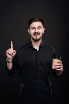 Retrato de um jovem bonito sorridente com bigode e barba segurando a xícara de café e levantando o dedo indicador enquanto tem uma ideia