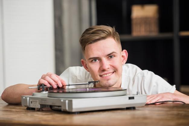 Retrato, de, um, jovem, bonito, sorrindo, homem, tocando, a, plataforma giratória, vinil, jogador registro