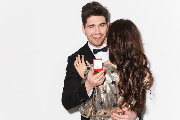 Retrato de um jovem bonito vestido de terno fazendo uma proposta com uma caixa de anel para uma garota isolada sobre o branco