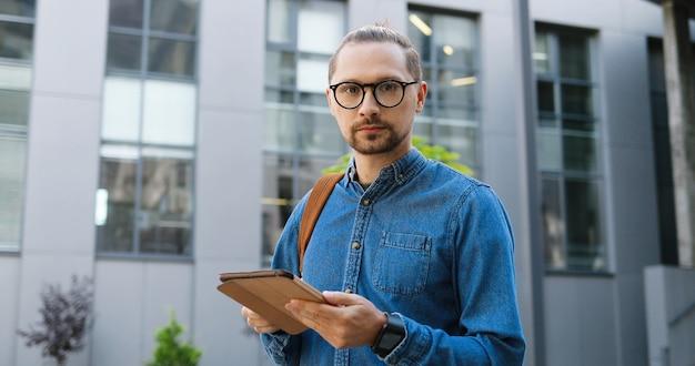 Retrato de um jovem branco em copos batendo no dispositivo tablet e sorrindo para a câmera na rua da cidade. mensagem de mensagens de texto masculina bonita e navegação no computador gadget ao ar livre. conceito de usuário do gadget.