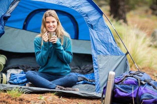 Retrato de um jovem caminhante bonito sentado em uma tenda