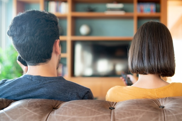 Retrato de um jovem casal a passar algum tempo juntos e a ver séries de televisão ou filmes enquanto está sentado no sofá em casa. novo conceito de estilo de vida normal.