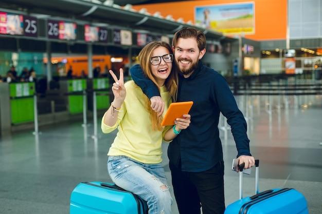 Retrato de um jovem casal abraçando no aeroporto. ela tem cabelo comprido, suéter amarelo, jeans e tablet. ele tem camisa preta, calça e mala perto. eles estão sorrindo para a câmera.