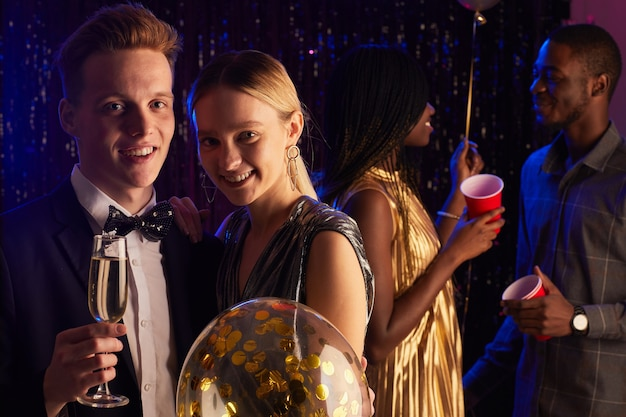 Retrato de um jovem casal adolescente sorrindo para a câmera enquanto desfruta da noite do baile, copie o espaço