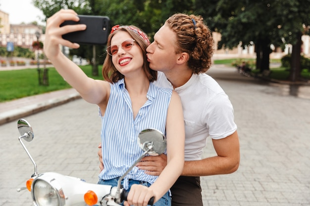 Retrato de um jovem casal adorável andando juntos em uma moto na rua da cidade, tirando uma selfie