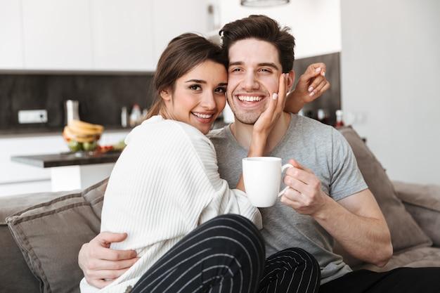 Retrato de um jovem casal adorável, bebendo café
