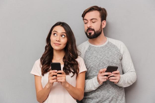 Retrato de um jovem casal adorável usando telefones móveis