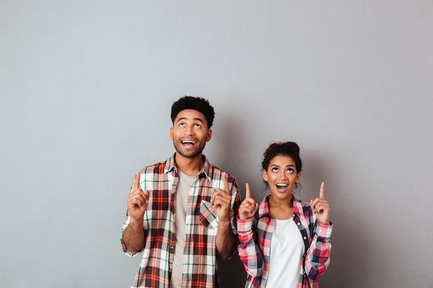 Retrato de um jovem casal africano animado apontando para cima com os dedos