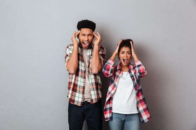 Retrato de um jovem casal africano assustado gritando