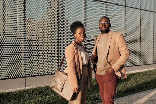 Retrato de um jovem casal africano em ternos elegantes, sorrindo para a câmera em pé na cidade