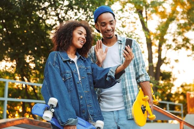 Retrato de um jovem casal africano feliz com skates
