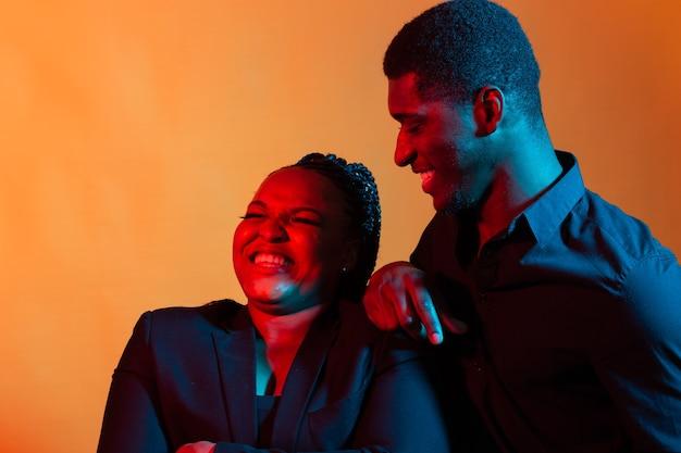 Retrato de um jovem casal afro-americano apaixonado posando vestida com roupas clássicas. néon