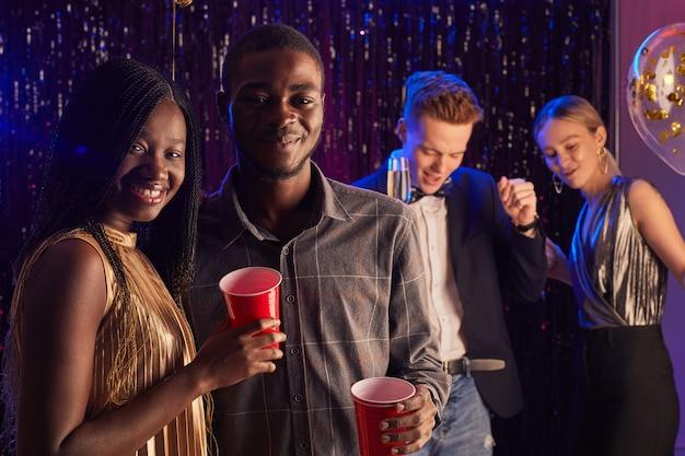 Retrato de um jovem casal afro-americano sorrindo para a câmera enquanto desfruta da noite do baile, copie o espaço