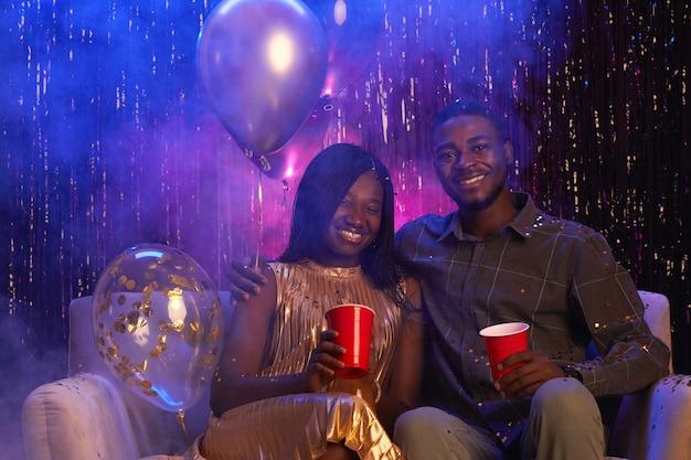 Retrato de um jovem casal afro-americano sorrindo para a câmera enquanto está sentado no sofá contra um fundo cintilante e curtindo a festa, copie o espaço