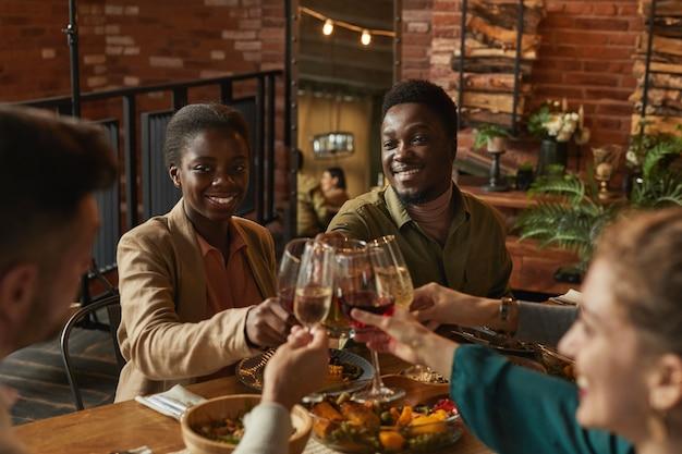 Retrato de um jovem casal afro-americano tilintando copos enquanto desfruta de um jantar com amigos e família em um interior aconchegante