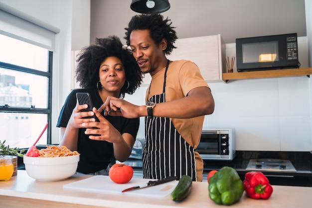 Retrato de um jovem casal afro cozinhando juntos e usando telefone celular na cozinha em casa.