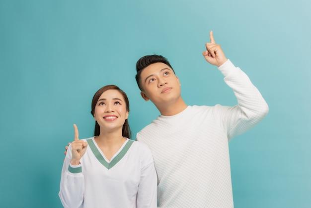 Retrato de um jovem casal alegre abraçando e apontando o dedo para cima