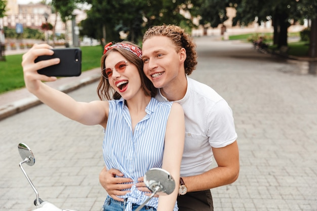 Retrato de um jovem casal alegre andando juntos em uma moto na rua da cidade, tirando uma selfie