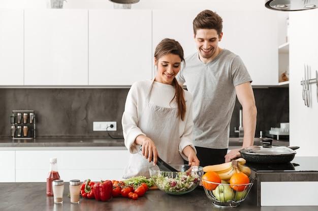 Retrato de um jovem casal alegre cozinhar