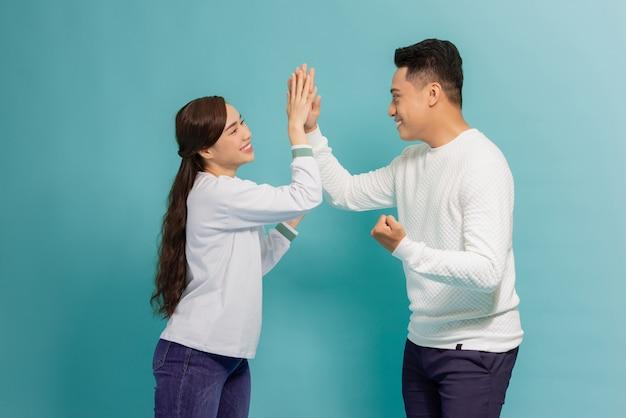 Retrato de um jovem casal alegre dando mais cinco sobre o azul