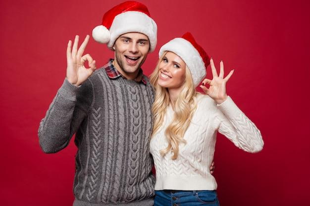 Retrato de um jovem casal alegre em chapéus de natal