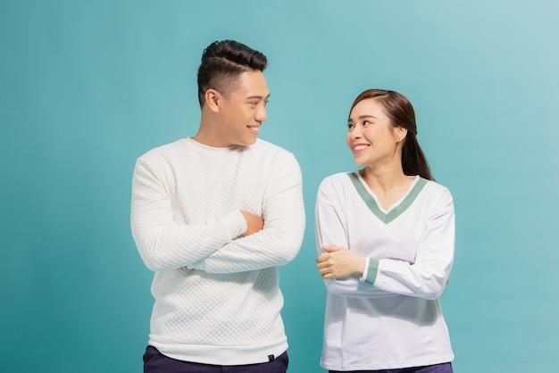 Retrato de um jovem casal alegre em pé com os braços cruzados e olhando um para o outro isolado sobre o azul